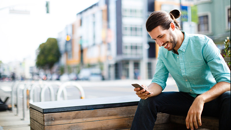 Seated man using smart phone in a city setting.